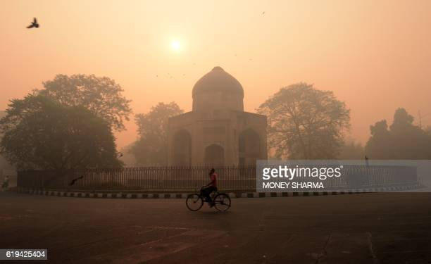 TOPSHOT An Indian cyclist rides along a street as smog envelops a monument in New Delhi on October 31 the day after the Diwali festival New Delhi was...