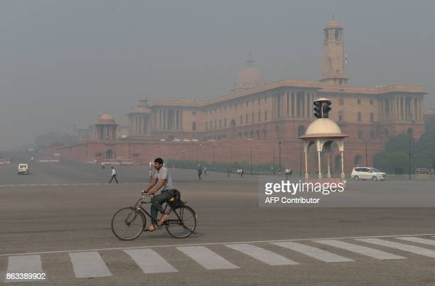 An Indian cyclist riding on a street amid heavy smog in New Delhi on October 20 2017 the day after the Diwali Festival New Delhi was shrouded in a...