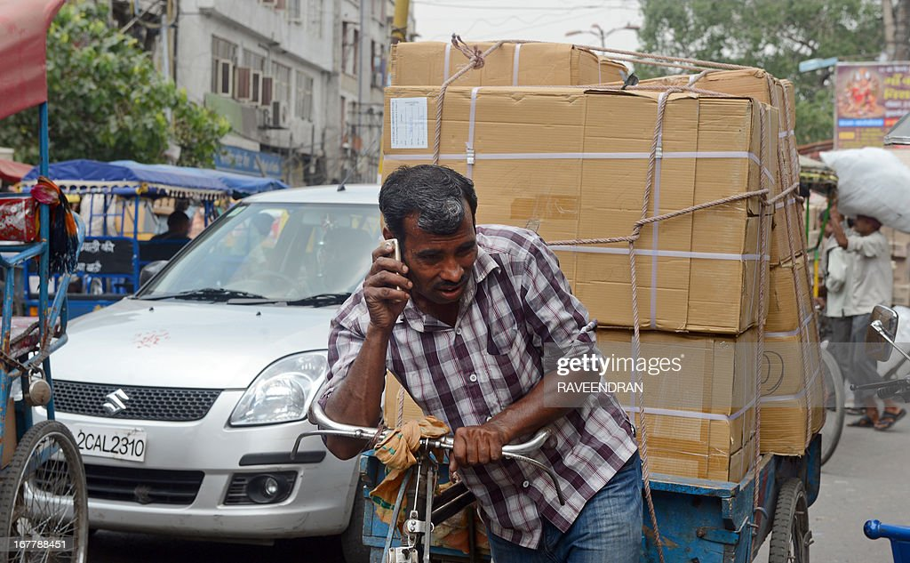 An Indian daily-wage labourer talks on his mobile phone as he transports goods on a rickshaw van down a busy street in New delhi on April 30, 2013. India's once-booming economy has slowed sharply due to high interest rates, Europe's debt crisis and sluggish investment caused by domestic and overseas concerns about policy-making and corruption.