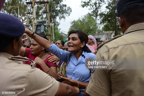 An Indian Dalit tries to barge inside a police station to free Dalit supporters who were detained by police for damaging vehicles and disturbing...