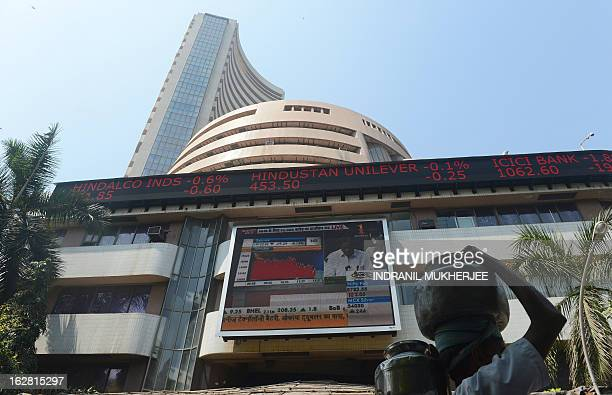 An Indian deliverman carries pots of drinking water past the digital broadcast on the facade of the Bombay Stock Exchange telecasting Indian Finance...