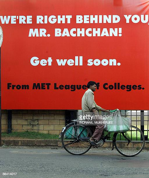 An Indian delivery man cycles past a hoarding put up for Bollywood movie legend Amitabh Bachchan outside a city hospital where he is recuperating...