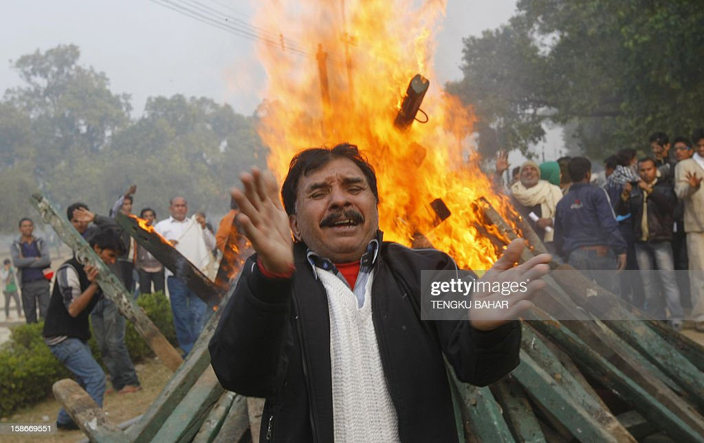 An Indian demonstrator chants slogans as protesters burn wooden poles that were torn down from barricades during a protest calling for better safety for women following the rape of a student last week, in front the India Gate monument in New Delhi on December 23, 2012. In the biggest protest so far, several thousand college students rallied at the India Gate monument in the heart of the capital where they were baton-charged, water cannoned and tear gassed by the police.