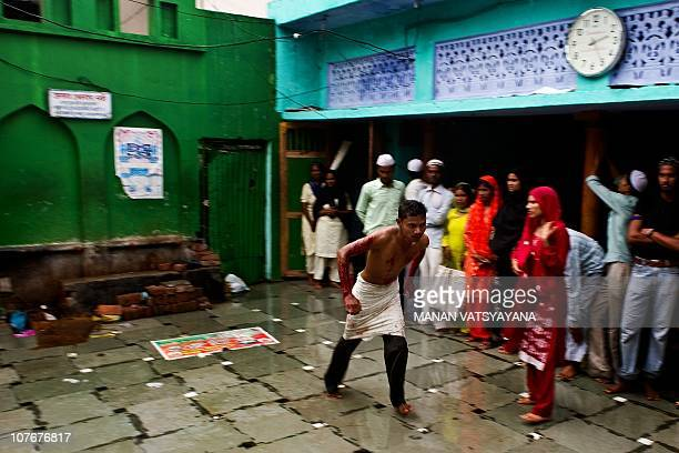 An Indian devotee believed to be possessed by evil spirits in a state of trance runs across the compund at the Hazrat Shahdana Wali Dargah in...