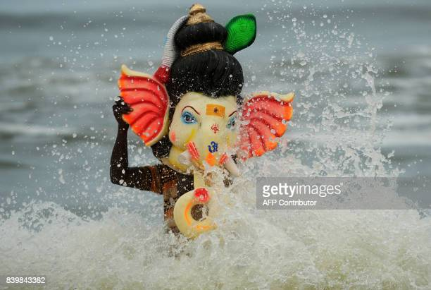 An Indian devotee carries an idol of elephantheaded Hindu god Ganesh for immersion in the Indian ocean at Pattinapakkam beach in Chennai on August 27...
