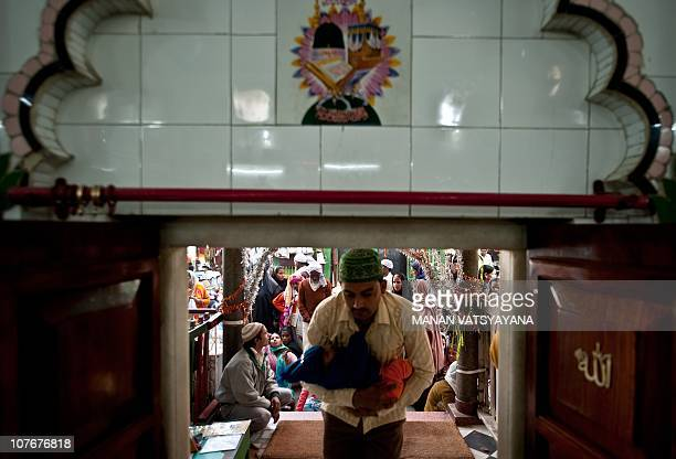 An Indian devotee carries his child to seek blessings at the Hazrat Shahdana Wali Dargah in Bareilly around 300kms from New Delhi on December 22010...