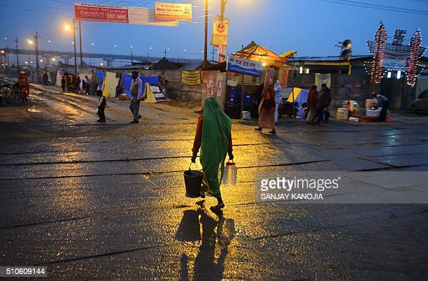 TOPSHOT An Indian devotee carries water through a camp used by those attending the Magh Mela after rainfall in Allahabad on February 16 2016 AFP...