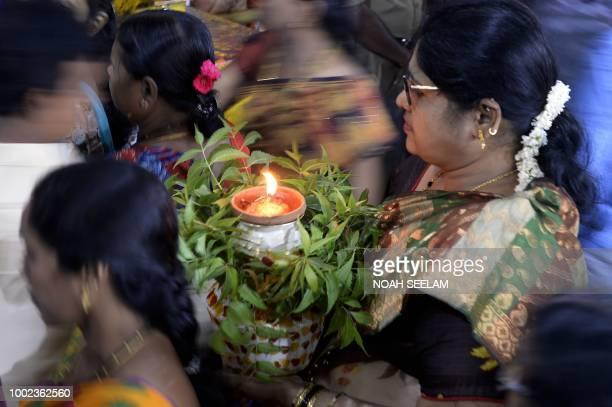 An Indian devotee carry a 'bonam' as she offers prayers for Hindu goddess Mahakali ahead of the Bonalu festival at Sri Ujjaini Mahakali Temple in...