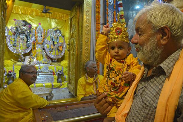 An Indian devotee carry his grandson dressed as the Hindu God Lord Krishna as they pay respects at the Durgiana Temple in Amritsar on August 25 on...