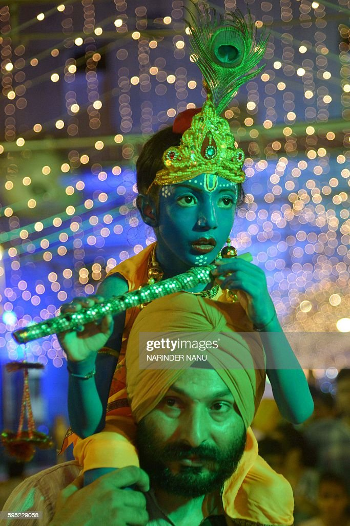 An Indian devotee carry his son dressed as the Hindu God Lord Krishna as they pay respects at the Durgiana Temple in Amritsar on August 25 on the...