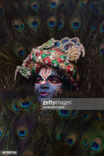 An Indian devotee dressed as Hindu deity Krishna participates in a Hindu religious procession on the occasion of the Ram Navmi festival in Amritsar...