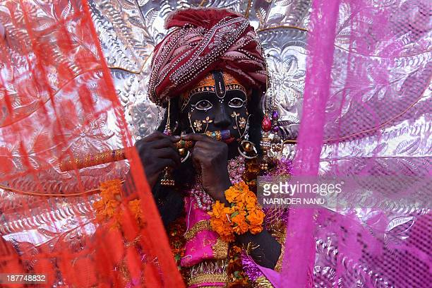 An Indian devotee dressed as Hindu Lord Krishna participates in a procession in Amritsar on November 12 on the occasion of the birth anniversary of...