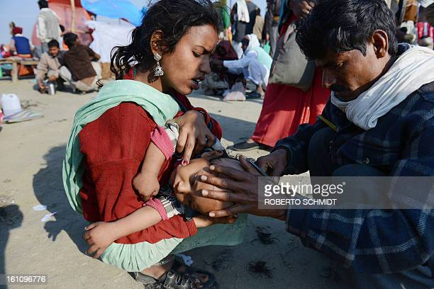 An Indian devotee holds her child as a man shaves his head on the banks of the river Ganges during the Kumbh Mela in Allahabad on February 9 2013...