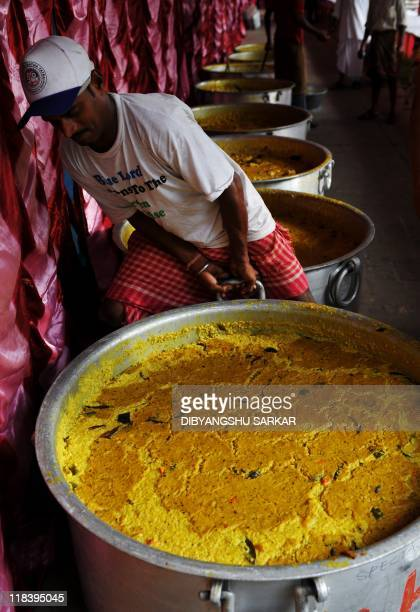 An Indian devotee of the Hindu god Krishna pulls a cauldron filled with cooked Prasad before distribution during the fifth day of the seven day long...