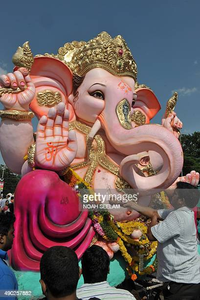 An Indian devotee offers pooja to an idol of Hindu god Lord Ganesh prior to immersion in the Hussain Sagar Lake during the Ganesh Chaturthi festival...