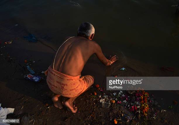 An indian devotee worships on the polluted bank of River GangesAllahabad on September 222015The Ganges is heavily polluted with raw sewage animal and...