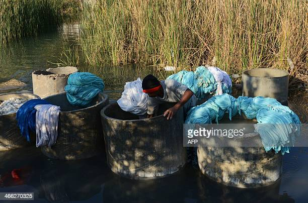 An Indian dhobi or washerman washes clothes at a Dhobi Ghat in Ahmedabad on February 1 2014 The tradition goes back centuries and is sustained in...
