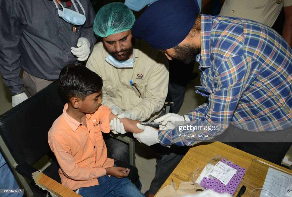 An Indian doctor collects blood from young boy Karan whose father Sonu went missing in Iraq at the Forensic Medicine and Toxicology Department of the.