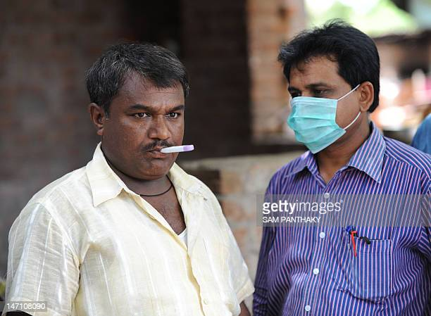 An Indian doctor examines the temperature of a villager of Kochariya in Bavla Taluka some 40 kms from Ahmedabad on June 25 2012 A local resident...