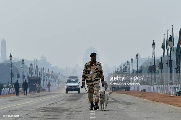 An Indian dogsquad personnel walks with a dog during an inspection at Rajpath where the nation's Republic Day celebrations will take place in New...