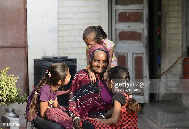 An Indian elderly woman interacts with her granddaughters in Suraj in Mehsana district some 100 km from Ahmedabad on February 20 2016 A village in...