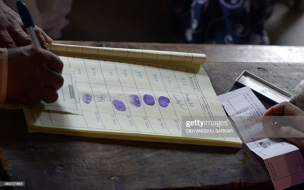An Indian election officer keeps a register of voters at a polling stating in Dibrugarh on April 7, 2014, during national elections. Indians have begun voting in the world's biggest election which is set to sweep the Hindu nationalist opposition to power at a time of low growth, anger about corruption and warnings about religious unrest. India's 814-million-strong electorate are forecast to inflict a heavy defeat on the ruling Congress party, in power for 10 years and led by India's famous Gandhi dynasty. AFP PHOTO/Dibyangshu SARKAR