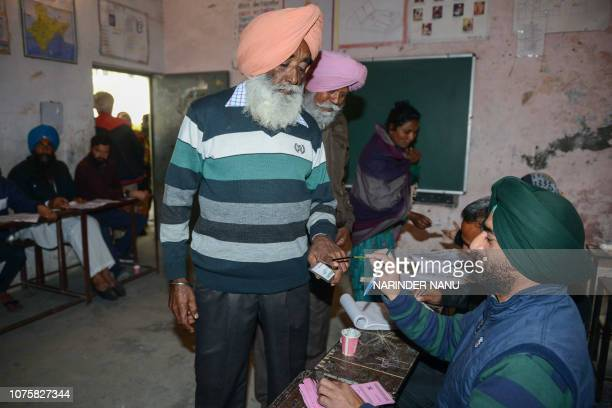 An Indian election officer marks the finger of a voter as he prepares to cast his ballot for Punjab local elections at a polling booth in a village...