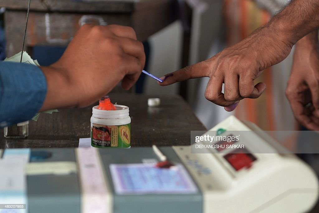 An Indian election officer marks the finger of a voter with ink at a polling stating in Dibrugarh on April 7, 2014, during national elections. Indians have begun voting in the world's biggest election which is set to sweep the Hindu nationalist opposition to power at a time of low growth, anger about corruption and warnings about religious unrest. India's 814-million-strong electorate are forecast to inflict a heavy defeat on the ruling Congress party, in power for 10 years and led by India's famous Gandhi dynasty. AFP PHOTO/Dibyangshu SARKAR