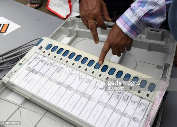 An Indian election official examines an Electronic Voting Machine at a distribution centre ahead of the third phase of India's general election at...