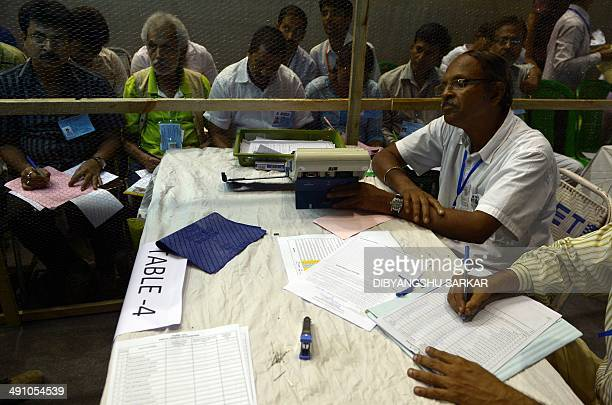 An Indian election official shows the results on an Electronic Voting Machine to polling agents at a counting centre in Kolkata on May 16 2014...