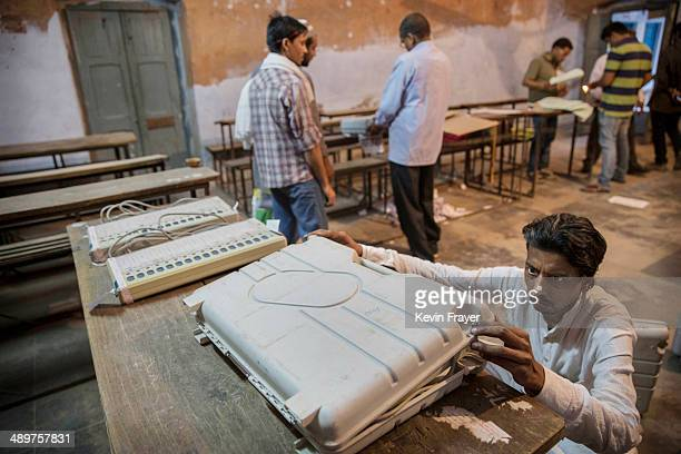 An Indian election worker closes up an electronic voting machine before sealing it after the final polls closed a polling station on May 12 2014 in...