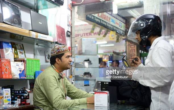 An Indian electronics vendor speaks with a customer at his outlet at Indira Bhawan in Allahabad on June 29 2017 India is bracing for upheaval as it...