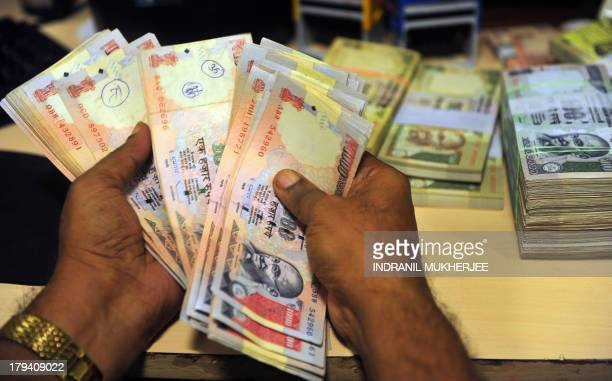 An Indian employee looks for illegal Indian rupee currency notes at a bank in Mumbai on September 3 2013 India's currency slid sharply and the share...