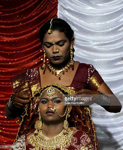 An Indian eunuch is assisted by another with wedding attire during their wedding reception in Ahmedabad on July 12 2009 In the presence of some one...
