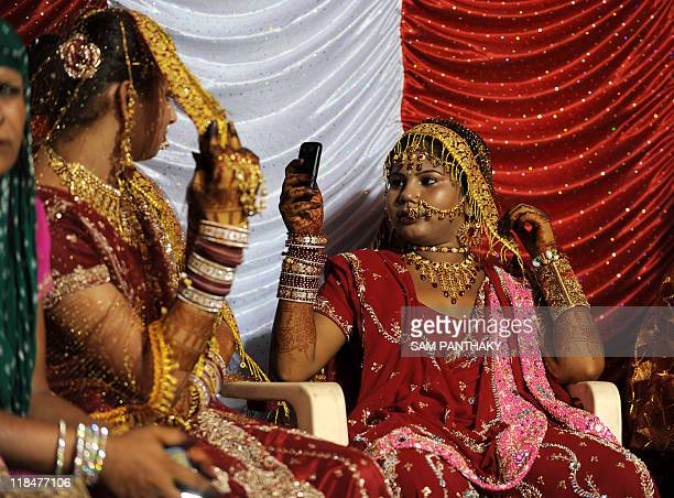 An Indian eunuch take pictures of another using a cellular telephone during their wedding reception in Ahmedabad on July 12 2009 In the presence of...