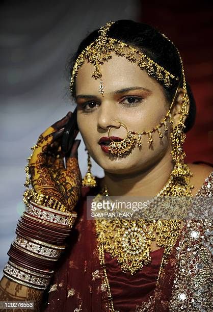An Indian eunuch uses a cellular telephone during a wedding reception in Ahmedabad on July 12 2009 In the presence of some one hundred eunuchs of the...