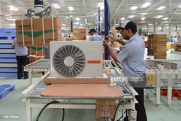 An Indian factory employee gives finishing touches to an air conditioner before final packing at the Hitachi Home and Life Solutions' air conditioner...