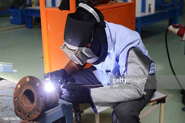 An Indian factory employee welds at the Hitachi Home and Life Solutions' air conditioner manufacturing facility near Kadi town some 50 kms from...