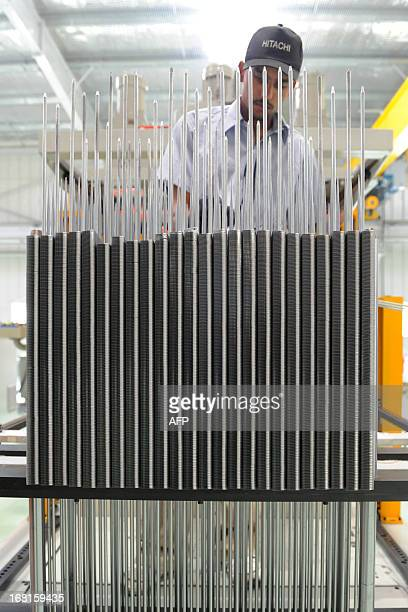 An Indian factory employee works on the assembly line at the Hitachi Home and Life Solutions' air conditioner manufacturing facility near Kadi town...