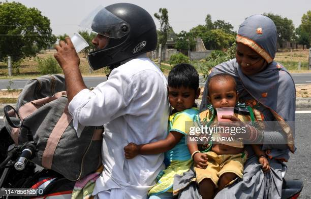 An Indian family drink free cold sweet water on a highway during a hot afternoon at Garhi village in the northern Indian state of Haryana on June 3...
