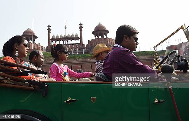An Indian family drives past the Red Fort prior to the start of the 21 Gun Salute International Vintage Car Rally in New Delhi on February 21 2015...