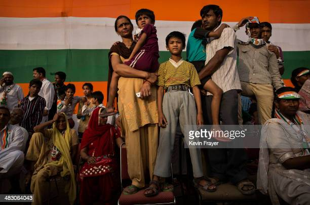 An Indian family listens as Rahul Gandhi leader of India's ruling Congress Party speaks at a rally on April 6 2014 in New Delhi India India will vote...