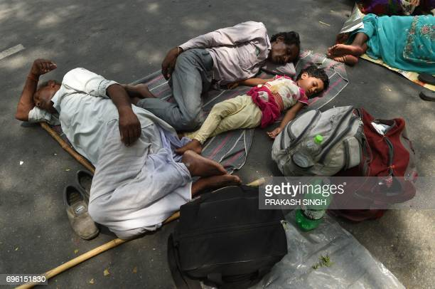An Indian family of farmers take a nap during a protest by the Bhartiya Kisan Union against Prime Minister Narendra Modi and the Madhaya Pradesh...