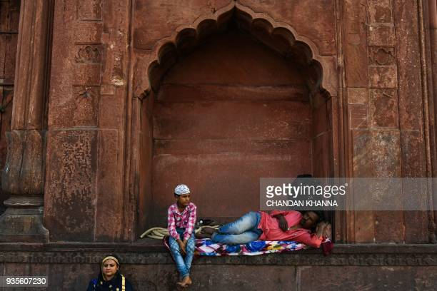 An Indian family rests inside Jama Masjid in the old quarters of New Delhi on March 21 2018 / AFP PHOTO / CHANDAN KHANNA