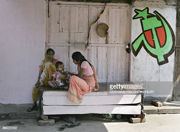 An Indian family sits beside Communist Party of India electionn graffitti at a slum area in Kolkata on April 18 2009 India holds its 15th...