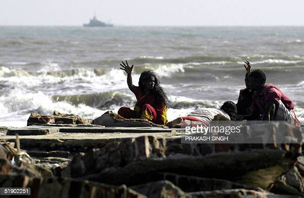 An Indian family sits on the remains of their flatened house in Akarapatti fishing colony on the seashore near Nagapattinam port some 350 km south of...