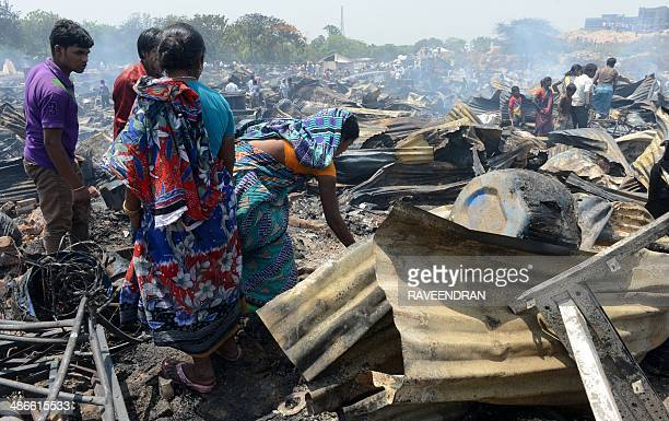 An Indian family sorts through the charred remains of their home after a fire broke out in a makeshift settlement in New Delhi on April 25 2014 More...