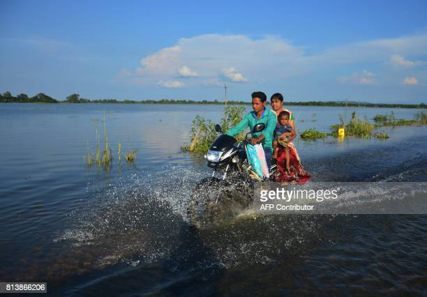 An Indian family travels along a flooded road on a motorbike in the district of Kamrup in Assam on 13 July 2017 Nearly half a million people in Assam...