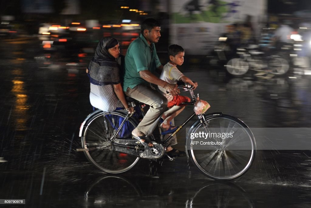 An Indian family travels on a bike as heavy rain falls in Jalandhar on July 6 2017 / AFP PHOTO / SHAMMI MEHRA