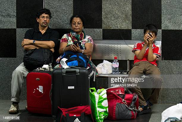 An Indian family waits for their train at a railway station following an overnight regionwide power outtage in New Delhi on July 30 2012 A massive...